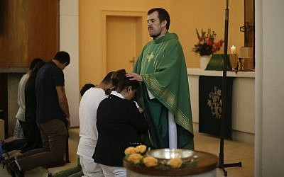 Pastor Gottfried Martens prays with people from Iran during a baptism service in the Trinity Church in Berlin, Aug. 30, 2015.  (AP/Markus Schreiber)