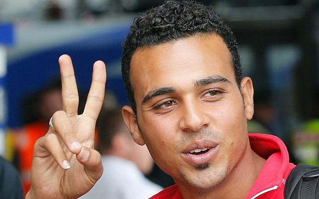 A young migrant flashes a victory sign as he arrives at the main train station in Munich, Germany, Saturday, Sept. 5, 2015. (AP Photo/Michael Probst)