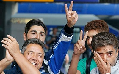 Refugees flash victory signs and wipe away tears as they arrive at the main train station in Munich, Germany, Saturday, Sept. 5, 2015. (AP Photo/Michael Probst)