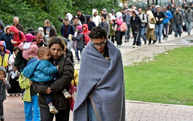 Migrants walk from the main train station in Dortmund, Germany, Sunday, Sept. 6, 2015. (AP Photo/Martin Meissner)
