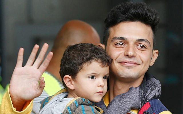 A father carries his child as they arrive at the main train station in Munich, Germany, Saturday, Sept. 5, 2015. (AP Photo/Michael Probst)