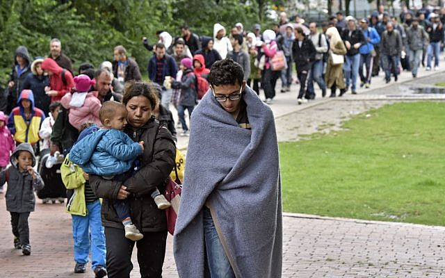 Illustrative photo of migrants walking from the main station in Dortmund, Germany, to a hall where they get first attendance, September 6, 2015. (AP/Martin Meissner)
