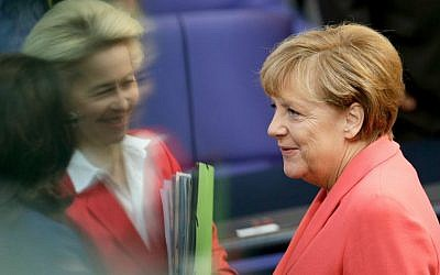 German Chancellor Angela Merkel (right), talks to German Defense Minister Ursula von der Leyen (second left) and German Labor Minister Andrea Nahles (left) as she arrives for a meeting of the German Federal Parliament at the Reichstag in Berlin, Germany, September 24, 2015. (AP/Michael Sohn)