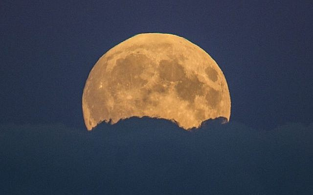 A full moon rises between clouds in Berlin, Germany, Sunday, Sept. 27, 2015. (AP/Gero Breloer)