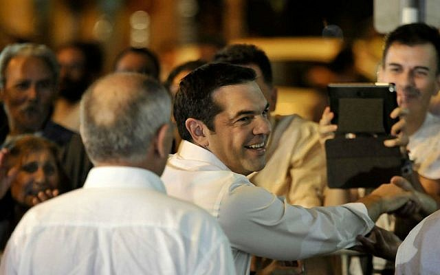 Leader of the left-wing Syriza party Alexis Tsipras shakes hands with a supporter as he arrives at the headquarters of his party in Athens, Sunday, Sept. 20, 2015. (AP Photo/Fotis Plegas G.)