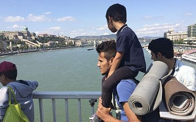 A man carries a boy on his shoulders as a group of hundreds of migrants crossed the river Danube in Budapest, Sept, 4, 2015, after they decided to walk toward Austria. (AP Photo/Bela Szandelszky)
