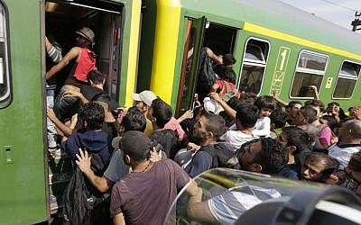 Migrants rush to board a train in Bicske, Hungary,  September 3, 2015. Over 150,000 migrants have reached Hungary this year, most via the southern border with Serbia. Many apply for asylum, but quickly try to leave for richer EU countries. (AP/Petr David Josek)