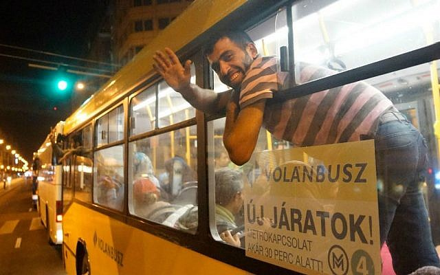 A migrant waves from the window of a bus of Volanbusz company at Keleti Railway Station in Budapest, Hungary, early Saturday, Sept. 5, 2015, after the Hungarian government provided buses to carry about 4,500 migrants to the Hungarian-Austrian border. (Zoltan Balogh/MTI via AP)