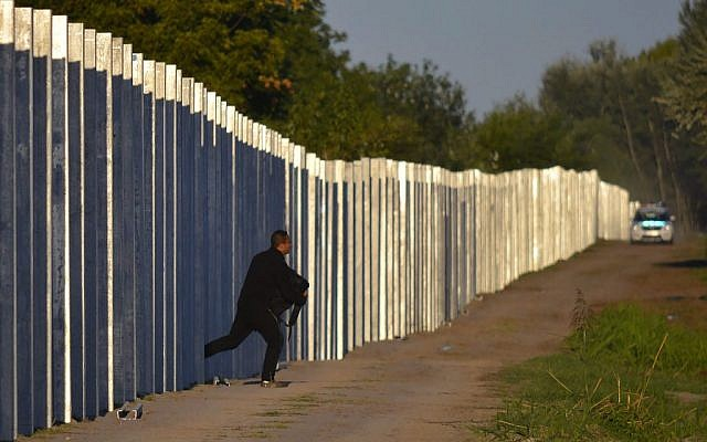 A migrant runs after he enters Hungary by crossing the temporary protection fence along the Hungarian-Serbian border as a police car approaches at Roszke, 180 kms southeast of Budapest, Hungary, Monday, September 7, 2015. (Edvard Molnar/MTI via AP)