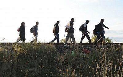 Migrants walk along the railway tracks connecting Horgos and Szeged in the vicinity of the Hungario-Serbian border near Roszke, 180 kms southeast of Budapest, Hungary, on September 8, 2015. (Zoltan Gergely Kelemen/MTI via AP)
