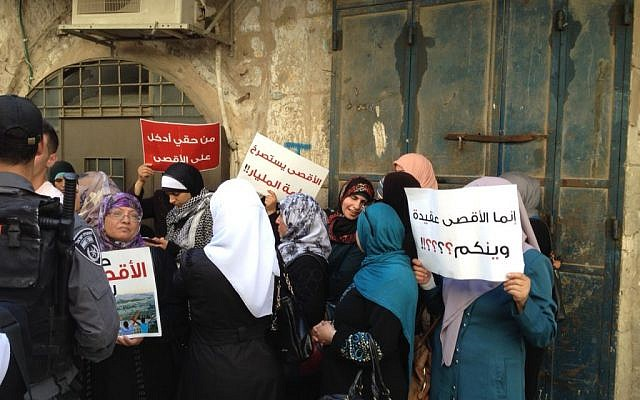 Murabitat activists hold signs reading 'it is my right to enter al-Aqsa' and 'al-Aqsa cries out to the nation of one billion,' September 2, 2015 (Elhanan Miller/Times of Israel)