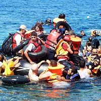 Staff from the IsraAid charity help refugees to reach the shore after their boat overturned off the Greek coast, September 13, 2015. (photo courtesy of IsraAid)