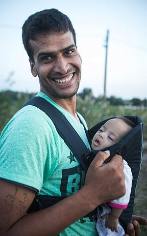 A Syrian father on the Hungarian-Serbian border after receiving a baby sling donated by Israelis via an IsraAID Facebook campaign, September 15, 2015. (Photo: IsraAID)