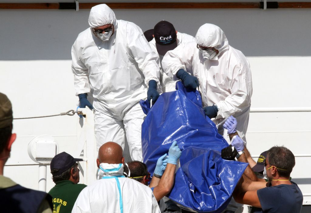 A body bag with a dead migrant is disembarked from the Italian Coast Guard ship Fiorillo in the harbor of Reggio Calabria, Italy, on August 28, 2015. (AP Photo/Adriana Sapone)