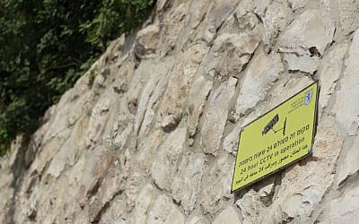 A sign warning stone-throwers that the area is under surveillance on the wall separating Armon Hanatziv from Jabel Mukaber, Sept. 16, 2015. (Judah Ari Gross/Times of Israel)