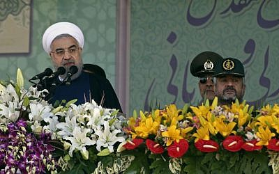 Iranian President Hassan Rouhani, left, speaks at a military parade marking the 35th anniversary of Iraq's 1980 invasion of Iran, attended by Revolutionary Guard commander Mohammad Ali Jafari, right,in front of the shrine of the late revolutionary founder, Ayatollah Khomeini, just outside Tehran, Iran, Tuesday, Sept. 22, 2015. (AP Photo/Vahid Salemi)