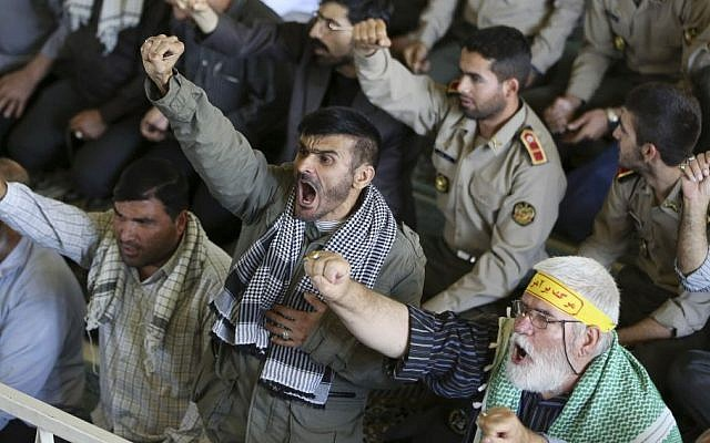"""Iranian worshipers chant slogans such as """"death to Al-Saud family,"""" a reference to the rulers of the Saudi kingdom, in a reaction to the hajj crush deaths in mid-September 2015, while they listen to the sermons of the Friday prayer in Tehran, Iran, Friday, Sept. 25, 2015. (AP/Vahid Salemi)"""