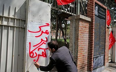 "An Iranian student writes an anti-US slogan in Persian which reads: ""Death to America"" at the gate of the former US Embassy where an anti-US plaque was unveiled in a ceremony, in Tehran, Iran, Wednesday, Sept. 2, 2015 [Ebrahim Noroozi/AP]"