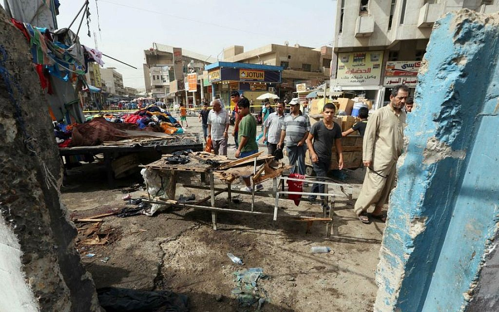 Civilians inspect the aftermath of a suicide bomb attack in Baghdad, Iraq, Thursday, Sept. 17, 2015. (AP Photo/Hadi Mizban)