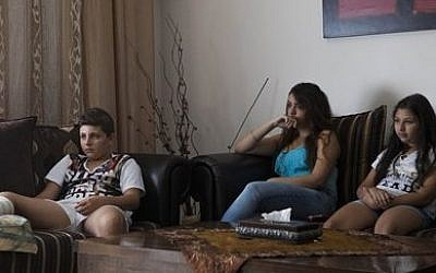From left, Bashar, Ranin, and Loucin Khoury watch television in their house In the central city of Ramle, September 22, 2015 (AP Photo/Dan Balilty)