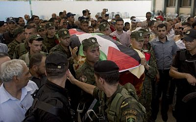 Palestinian security officers carry the body of Riham Dawabsha, 27, during her funeral procession in the West Bank village of Duma, near Nablus, Monday, Sept. 7, 2015. (AP/Nasser Nasser)