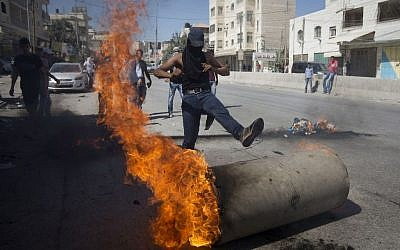 Palestinians clash with Israeli troops at Qalandia checkpoint between Jerusalem and the West Bank city of Ramallah, Friday, Sept. 18, 2015. (AP Photo/Majdi Mohammed)