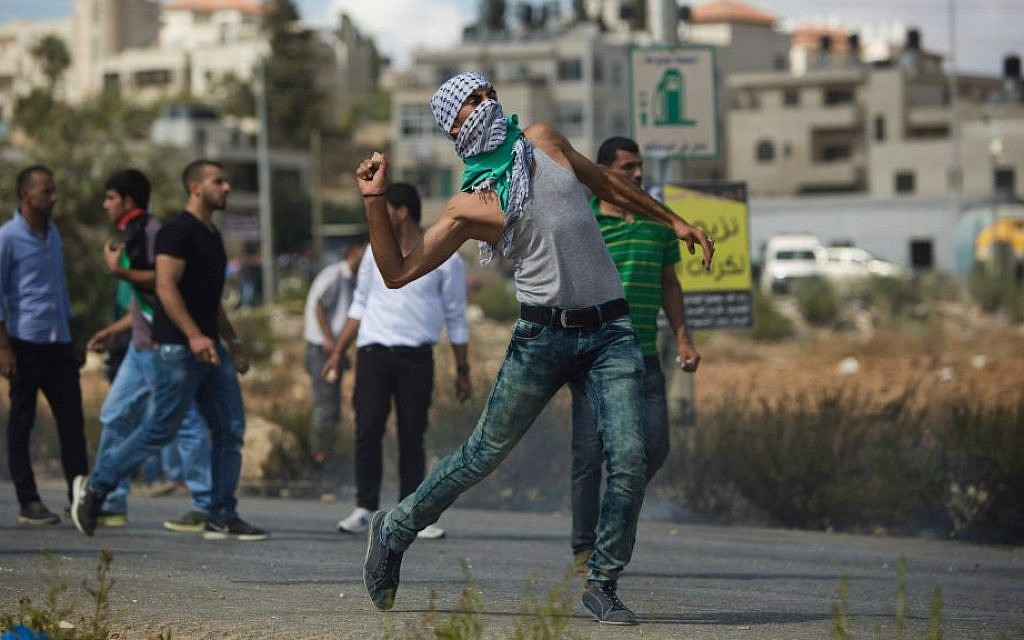 A Palestinian demonstrator hurls a stone during clashes with Israeli troops near Ramallah, Tuesday, Sept. 29, 2015. (AP Photo/Majdi Mohammed)