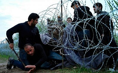 Syrian refugees cross into Hungary underneath the border fence on the Hungarian-Serbian border near Roszke, Hungary, Aug. 26, 2015 (AP Photo/Bela Szandelszky, File)