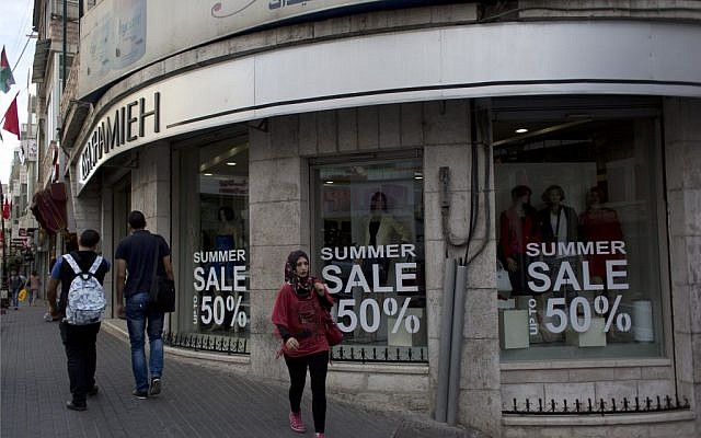 Palestinian walk past a boutique in the West Bank city of Ramallah, Tuesday, Sept. 29, 2015. (AP/Nasser Nasser)