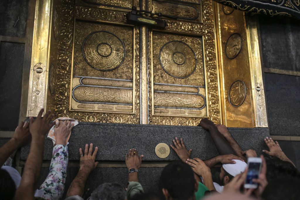 In this Monday, Sept. 21, 2015 photo, Muslim pilgrims pray as they touch the Kaaba, the cubic building at the Grand Mosque in the Muslim holy city of Mecca, while performing Tawwaf, an anti-clockwise movement around the Kaaba during the annual Pilgrimage, known as hajj, in Saudi Arabia. (AP Photo/Mosa'ab Elshamy)