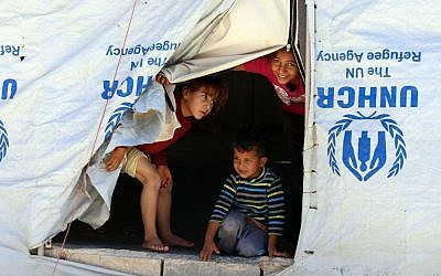 Syrian refugee children look from their tent during a visit by UN humanitarian chief Stephen O'Brien to the Zaatari Refugee Camp, near Mafraq, Jordan, Saturday, Sept. 19, 2015. (AP Photo/Raad Adayleh)