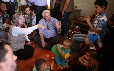 UN humanitarian chief Stephen O'Brien, center, visits with Syrian refugees who fled civil war in their country, in the Zaatari Refugee Camp, near Mafraq, Jordan, Saturday, Sept. 19, 2015.  (AP Photo/Raad Adayleh)