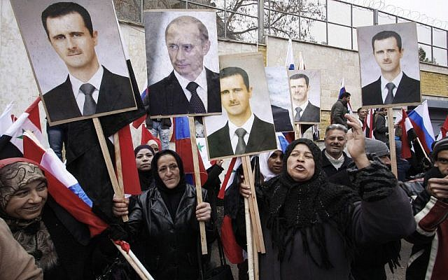 In this Sunday, March 4, 2012 file photo, Syrians hold posters of Syrian President Bashar Assad, far left, and Russian President Vladimir Putin, second left, during a pro-Syrian government protest in front of the Russian Embassy in Damascus, Syria. (AP/Muzaffar Salman, File)
