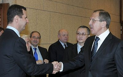 Syrian President Bashar Assad, left, shakes hands with Russian Foreign Minister Sergey Lavrov after talks in Damascus, Syria on February 7, 2012 (AP/Pool, File)