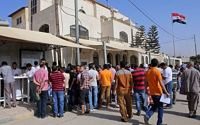 Syrian refugees gather outside their embassy waiting to apply for passports or to renew their old ones in Amman, Jordan, on September 15, 2015. (AP/Raad Adayleh)