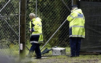 Police stand at the shut gates at Hamilton Zoo after a female zookeeper was killed by one of the tigers at the zoo in Hamilton, New Zealand Sunday Sept. 20, 2015. (Nick Reed/New Zealand Herald via AP)