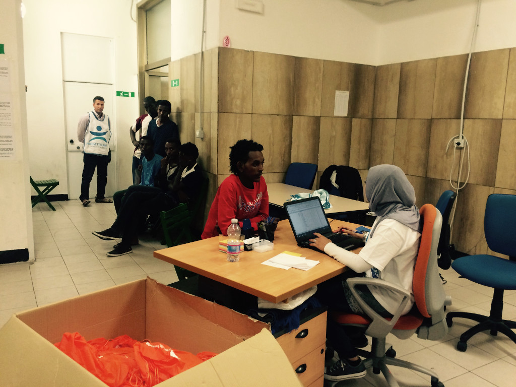 Twenty-eight-year-old Rima registers an Eritrean migrant. Rima works for Arca, the Italian NGO which was chosen by Milan's municipality to run the migrant registration facility. (Rossella Tercatin/The Times of Israel)