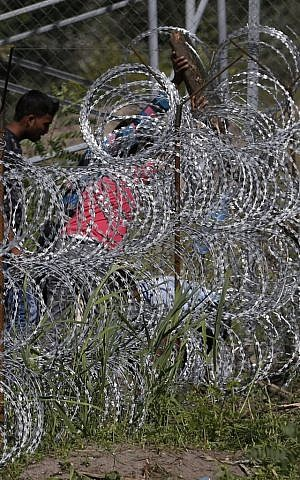 People try to cross under a wire fence on the Serbian border with Hungary, near the village of Hajdukovo, Serbia, Monday, September 7, 2015. (AP/Darko Vojinovic)