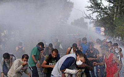 Hungarian police spray water on migrants at the 'Horgos 2' border crossing into Hungary, near Horgos, Serbia, Wednesday, September 16, 2015. (AP Photo/Darko Vojinovic)