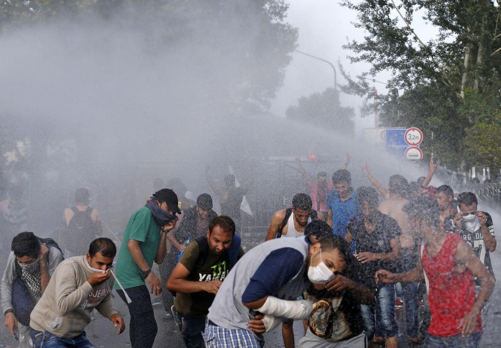 Hungarian police spray water on migrants at the 'Horgos 2' border crossing into Hungary, near Horgos, Serbia, Wednesday, September 16, 2015. (AP Photo/Darko Vojinovic)