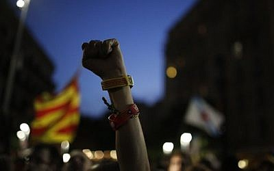 "A Catalonian independence supporter wearing a bracelet with the ""estelada"" or pro-independence flag colors, raises her fist during reactions after the vote in Barcelona, Spain, Sunday September 27, 2015 (AP Photo/Emilio Morenatti)"