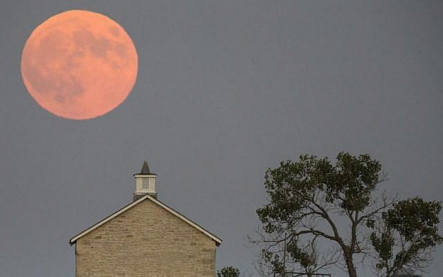 A super moon rises over the Lower Fox Creek School near Strong City, Kan., Sunday, Sept. 27, 2015. It was the first time Sunday since 1982 that a total lunar eclipse was combined with a supermoon. (Travis Heying/The Wichita Eagle via AP)