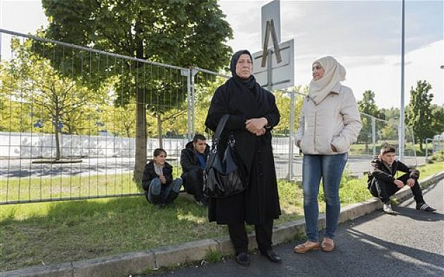 From left, Raghad, Mohammed, mother Khawla Kareem, Reem and Yaman, a refugee family from Syria, wait outside an asylum seekers shelter in Heidenau, near Dresden, eastern Germany, Sept. 22, 2015 photo  (AP Photo/Matthias Rietschel)