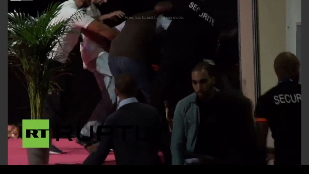 A man in a white shirt (second from left) is seen kicking two Femen activists (hidden from view by security personnel in black shirts) during a conference at the Muslim Salon in Pontoise, near Paris on Saturday, September 13, 2015. (Screen capture Liveleak)