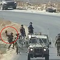 A still image taken from footage shot in the West Bank on September 25, 2015, shows an IDF soldier hurling a camera belonging to AFP reporters to the ground. (screen capture: YouTube)