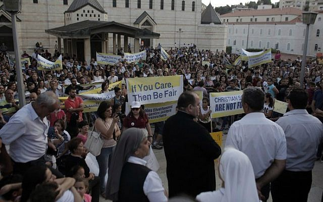 Hundreds of Arab Israeli Christians hold banners in a rally against what they said was state discrimination in funding their schools at the foot of the Basilica of the Annunciation in Nazareth on September 1, 2015 (AFP PHOTO / AHMAD GHARABLI)