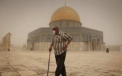 A Palestinian man wears a mask to protect his face from the dust as he walks past the Dome of the Rock mosque in the al-Aqsa Mosque compound, during a sandstorm on September 8, 2015, in the old city of Jerusalem. (AFP/AHMAD GHARABLI)