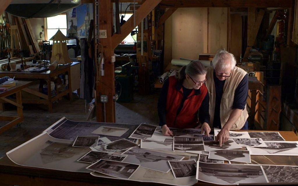 Artists Rick and Laura Brown review details on photographs of the Polish synagogues that no longer exist to aid in the reconstruction of the Gwoździec synagogue. (Trillium Studios production)