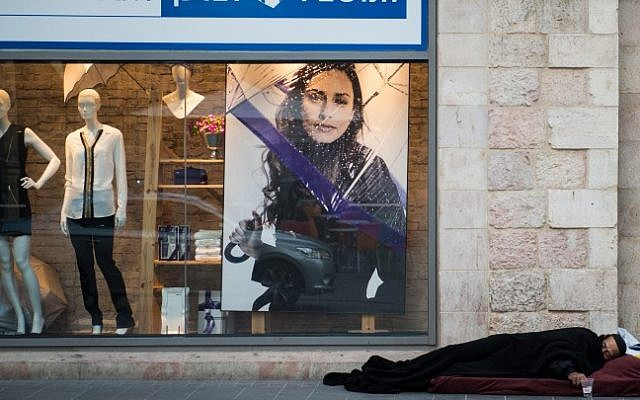 A homeless man sleeping in front of a department store in Jerusalem on December 4, 2014. (Danielle Shitrit/Flash90)