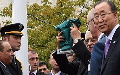 Palestinian Authority President Mahmoud Abbas raises the Palestinian flag as UN Secretary General Ban Ki-moon looks on during a ceremony in the rose garden of the UN's New York headquarters, September 30, 2015. (AFP PHOTO/TIMOTHY A. CLARY)